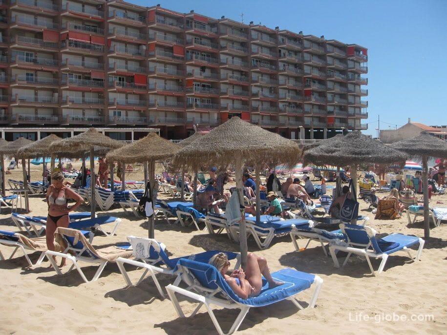 Шезлонги и зонты от солнца на пляже Лос Локос в Торревьехе