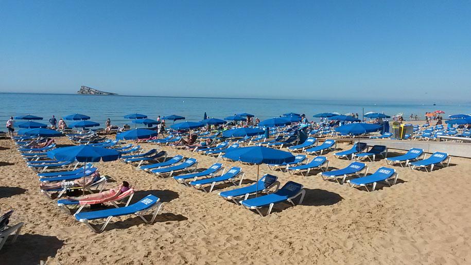 Шезлонги и зонты от солнца на пляже Леванте, Бенидорм, Испания